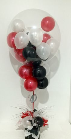 Red, black and white balloon table decoration using deco a deco bubble on top.