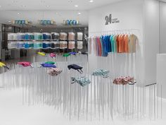 24 Issey Miyake by Nendo (Shibuya);   Shelving and hanger rods are also made of steel rods, in the 7 mm diametre common to all of the 24 Issey Miyake shop interiors. Supported by 'points', rather than by surfaces or lines, the bags seem to waft in the air like flowers in a light breeze, creating the illusion of a field of flowers in the store.