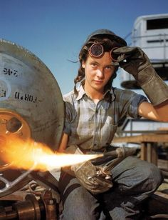 A welder at a boat-and-sub-building yard adjusts her goggles before resuming work, October 1943
