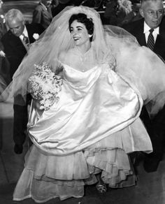 Elizabeth Taylor enters the Church of the Good Shepherd in Beverly Hills for her first wedding. The gown, a gift to Taylor from MGM and designed by costume designer Helen Rose, is made of 25 yards of satin with a 15-foot train. It's corseted and embellished with bugle beads and seed pearls. It is expected to fetch about $75,000.