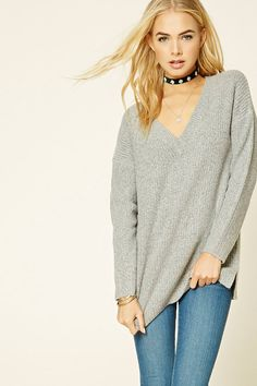 An oversized ribbed knit sweater featuring a V-neckline, dropped sleeves, side slits, and a longline silhouette.