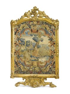 A GERMAN ROCOCO CARVED GILTWOOD FIRE SCREEN MID-18TH CENTURY upholstered à châssis with gros-point and petit-point wool and silk needlework panel, probably French, circa 1700.