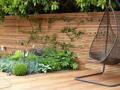 sichtschutz zaun holz material minimalistisch beet pflanzen parkett sitzschaukel