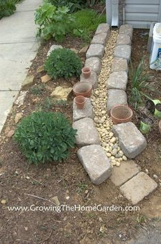 Gutter Drainage Path.......this is so much more attractive than our corrugated tubing. And you can keep a few pots watered too!