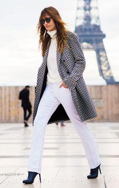 Caroline de Maigret wears a neutral turtleneck, checked coat, white jeans, and black boots