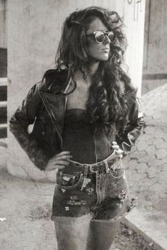 Could she look any cooler? 80's fashion: bodice, denim shorts, leather jacket and wild hair.