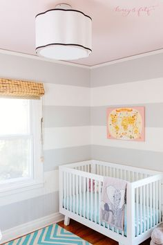 This modern, striped elephant safari-themed nursery features a blush pink ceiling and fab drum light!