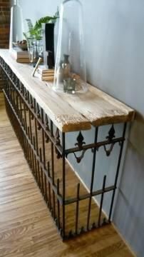 Uma grade de ferro velha sustenta uma madeira reaproveitada como aparador.