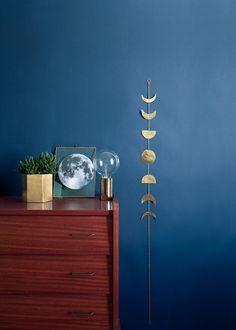 Commode sur mur bleu nuit, sur lequel est accroché un mobile en laiton en forme de quarts de lune.