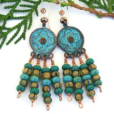The BOHO BEAUTIES handmade earrings have so many stylish, fun design elements going for them that you will want to wear them constantly! What first catches your eye are the ancient looking, turquoise green patina Mykonos chandelier pieces with a beautiful rounded cross design. Hanging from the gypsy-inspired charms are jauntily swinging lines of Picasso finish Czech glass beads in weathered turquoise, teal and striped beige.