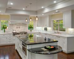 The island's granite countertop offers a contrast to the white cabinets and quartz countertops, while layered lighting keeps the kitchen brightly lit. Multiple sinks and work areas make this a versatile, functional kitchen.