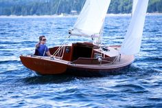 This is an Alerion 26 (the number suggests the length, more or less).  This is a beautiful sloop, perfect for daysailing.  Jimmy Buffett owns one named Savannah Jane.  I can't even imagine keeping up all that brightwork, espcially since I'm not Jimmy Buffett.