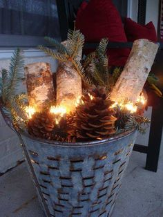 Wood or metal basked, fill with logs, pine cones and white lights . . . perfect for Christmas decorating.