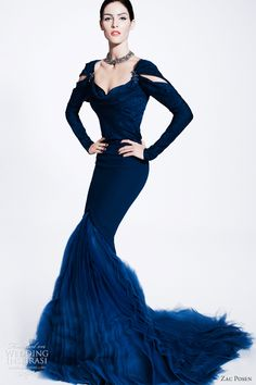 Deep blue mermaid gown with cutouts at the long sleeves.