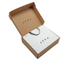 Luxury retail bags & mailing cartons for Atea. Off white Kraft paper with black foil blocking and paper twist handles. Corrugated mailing packs with black flex print.