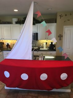Nautical Baby Shower- We turned the island into a sailboat and used it to serve the food buffet style. I measured and cut a table cloth for the sail, used scrapbook paper and white string for the flag line and a red table cloth that I pinned up to look round.  True story- for the port holes I traced a pot lid and cut them out of computer paper and duct taped on the red table cloth!