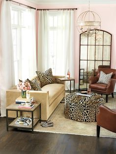 Living room with velvet sofa, pink walls, and leopard print accessories