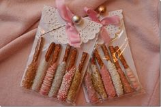 These are too cute.  Pretzel sticks are dipped in white chocolate and then sprinkled with nonpariels, glitter sugar and drizzled chocolate.  Card stock has been placed behind them for strength, cellophane bags and doilies are from Michael's Craft Store.