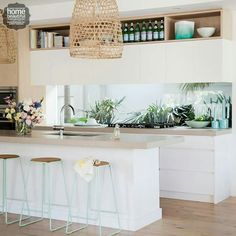 White cupboards, wooden bench tops and lights that link to the wood