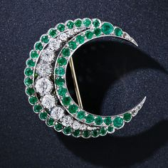 Compared to their ruby and sapphire cousins, emerald and diamond crescent brooches are relatively rare. This very lovely slice of the moon is crafted in platinum over gold and dates back to the late nineteenth century Victorian period. Twelve old mine-cut diamonds sparkle from above and between two outer rows of bright green emeralds. The pin back is removable and a flip-up loop is provided to allow for it to be worn as a pendant. 1 3/16 inches.