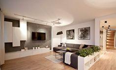 salon moderne avec parquet, canapé gris, meuble TV bas et colonnes en blanc et écran plat mural