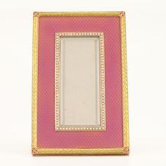 A Fabergé two color gold and enamel photograph frame, workmaster Michael Perchin, St Petersburg, circa 1890. Rectangular, in pink translucent enamel over an engine turned ground, the aperture framed in seed pearls, with a yellow gold laurel border and rose gold foliate corners, the back with an unusual lyre-form strut, suggesting that it was commissioned for a musician.