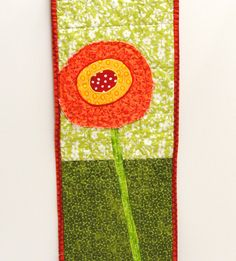 poppy wall quilt- single stem orange, yellow and red poppy on green, wall art, wall hanging. $33.00, via Etsy.