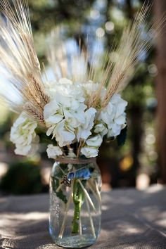 Wheat and hydrangeas in twine wrapped mason jars with ribbon