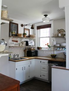 To modernize the kitchen and open up the space, the owners install open shelving, repaint the lower cabinets and replace the counter with a hand-me-down butcher block. Even with a splurge on vinyl floor tiles, they keep the budget to $3,400. See more before-and-after photos of this kitchen at Christina's Adventures.