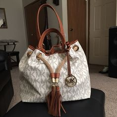 Micheal kors large leather bag Large leather bag with the MK letters all on the bag, leather straps and tassels and rope like draw for closer and  gold details . No marks on the outside or scuffs inside has a red stain maybe from something I had in bad?? But it don't seep through the bag at bottom can probably be wiped out? I have not tried it. Other then that bad is in excellent condition. I no longer have the dust bag or the receipt Please no low balling ladies or I won't reply back. Thank…