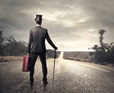 stock photo of man with vintage suitcase suit and cane looking at empty road