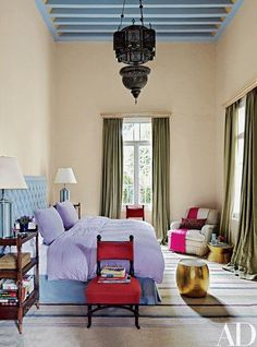 The antique lantern and the brass stool in the master bedroom are Lebanese. The ebonized slipper chairs are Italian, and the club chair, by O. Henry House, is clad in a Robert Kime ticking stripe | Ivory, lavender, blue, green, red.
