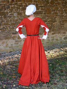 A German gown from the end of the fifteenth century with characteristic deep, pointed décolletage and original sleeve construction. The sleeves are slashed and laced together in three places. The skirt is widened by four gores and has a small train.