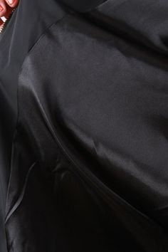 This plus size bomber jacket features a bomber shawl collar, slant hand pockets with snap-flap detail, zipper front closure, and long sleeves with zip media pocket at left. Completed with a contrasting ribbed knit trim along cuffs and neckline. Drawstring tie hemline. Fully lined. Accessories sold separately.