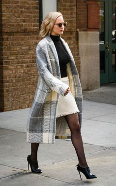 En route to a press event for her film Joy, Lawrence was all bundled up in a plaid shawl coat, black turtleneck, white tweed skirt, tights, and ankle boots. For a pop of color, she threw on mirrored round shades AKA our last-night-was-mad-real-go-to.