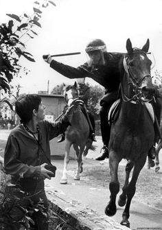 A mounted British police officer aims his truncheon at a female photographer during a 6,000 officer charge on the picket line of 5,000 striking coal miners, who'd been unlawfully preventing strike-breaking trucks from accessing their plant in Orgreave, South Yorkshire. 18 June 1984