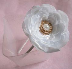 Tiara forrada com fita de cetim, com uma flor de cetim branca e miolo trabalhado com miçangas prateados douradas. Serve tanto para crianças quanto adultas. diâmetro da flor: aproximadamente 8,5 cm.