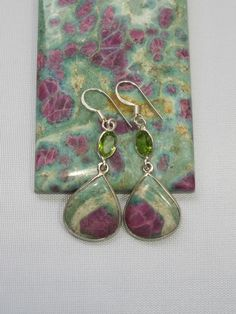 Drop earrings hand-set with Ruby in Fuchsite gemstones, adorned with faceted…