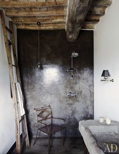 A guest bathroom features a concrete-and-resin shower and an antique stone sink | archdigest.com