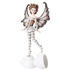 This fun fairy is perfect for anyone with a love of caffeinated beverages! The pixie has an espresso theme, with wings and an outfit in shades of brown, black and white. She stands upon two small mugs. The perfect figurine for any faery lover's collection!