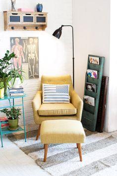 Желтое кресло вместе с напольным светильником, размещенные в углу комнаты, образуют отдельный уютный уголок