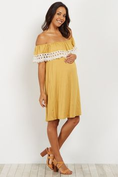 b24ba381752 Solid off shoulder maternity dress. Flounce on neckline with crochet trim.  Cinched neckline.