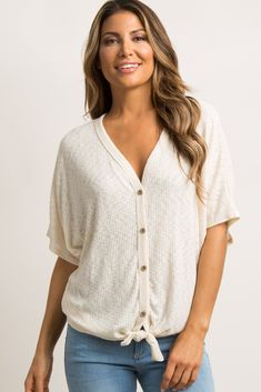 A ribbed, knit top featuring 3/4 dolman sleeves, a button front accent with a tie detail on hem, and a v-neckline.