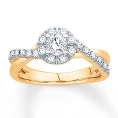 This gorgeous yellow gold engagement ring features round diamonds that sweep along the band to encircle an elegant center diamond.