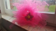Wreath with fuschia tulle. I caught the tulle into symmetrical pieces 20cm and tied them over the 12cm yarn.Then hot glued a satin ribbon the yarn made flower,complemented with a ribbon for hanging and voila!Ready for Ingrid's room!