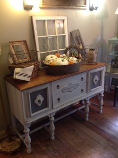 Milk painted buffet with fall/harvest decor incorporating old frames and a window