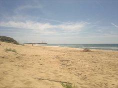 Playa de Zahora con faro de Trafalgar al fondo.