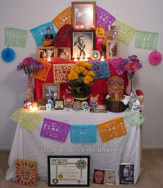Esta es una altar donde la gente usa papel picado fotos de calaveras y fotos de los difuntos con veladoras flores y calaveras de dulce.