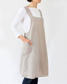 Item description This A-line apron dress was made with medium-weight linen and features two pockets on the sides. Wear it by slipping it over your head. It crosses in the back and is very comfortable to wear as there are no straps constraining your neck. Material 100% Medium-weight natural linen Linen is a natural fabric made of flax fibers and it is known for its durability and long life. It rapidly absorbs moisture and dries quickly. It is hypoallergenic, anti-bacterial and also a good…