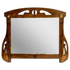 ESPEJO DE PARED AÑOS 20 En madera de caoba, con decoración tallada, calada y apliciones en metal patinado. Medidas: 67 x 75 cm.